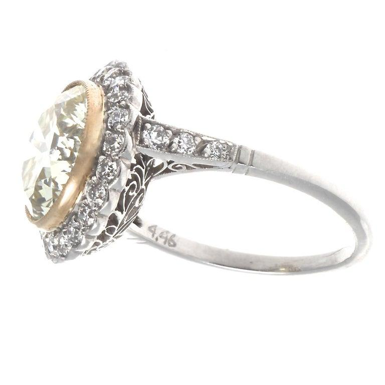 When bigger is better, this Art Deco revival diamond platinum ring delivers. Featuring a 4.46 carat old European cut diamond, graded S-T color, VVS clarity. Surrounded by 28 old European cut diamonds graded G-H color, VS clarity. Circa 2000s. Size 6