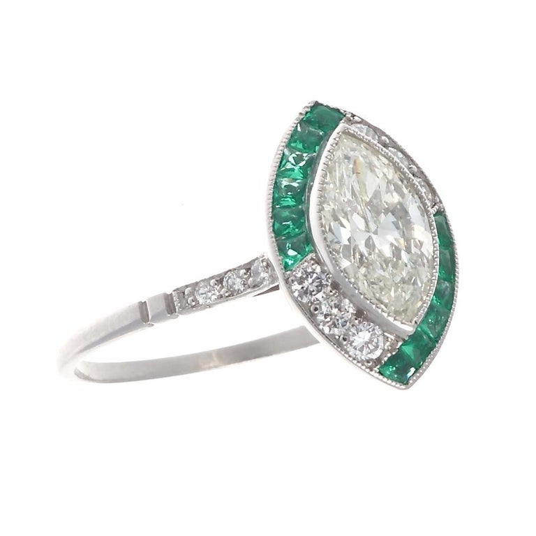 The perfect way to say I love you. Featuring a 0.94 carat marquise cut diamond that is J color, VS1 clarity. Surrounded by sparkling emeralds and diamonds. Crafted in platinum. Ring size 7 and can easily be resized, if needed this would come