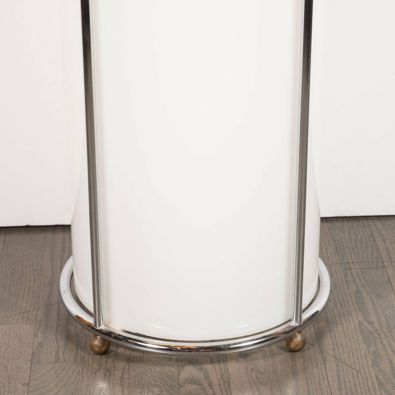 This gorgeous Art Deco pedestal offers a cylindrical opaque white plexi body with a circular polished chrome wrapped base and top, as well as spherical ball feet, also in chrome. Cylindrical chrome supports connect the base and the top, creating a