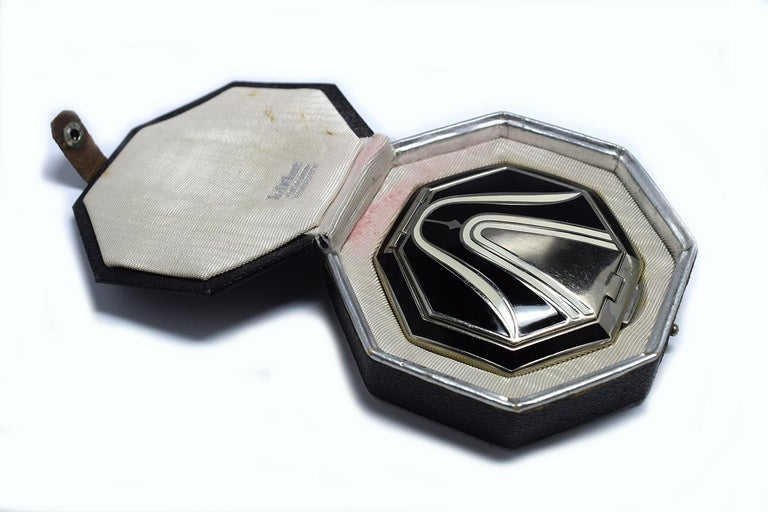 An Art Deco Richard Hudnut Le Debut 'Tulip' compact of octagonal form, with black and ivory colored enamelled decoration, fitted in original black leatherette box with paper label. Designed for Richard Hudnuts Deauville Line, the rouge and makeup