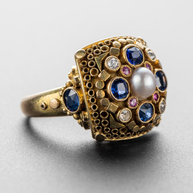 This original Elmar Seidler ring is composed of high-karat gold (at least 18K) that has been intricately and meticulously worked by Seidler to create a ring that defies categorization. Small geometric forms adorn the face of the ring, granulation