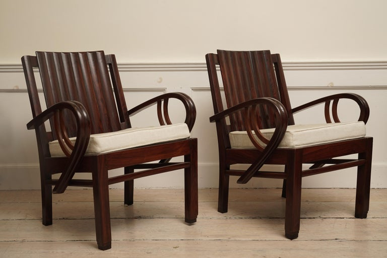 An incredible Art Deco rosewood suite of three pieces loveseat and pair of chairs. Slatted back with curled arms and stepped feet. The loveseat is 51