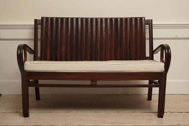 A lovely Art Deco rosewood loveseat. Great styling with slatted back, curled arms and stepped feet. The loveseat is 51