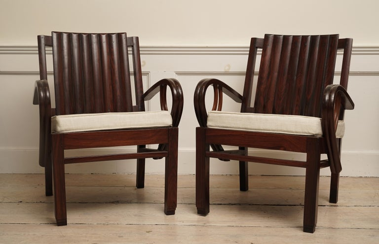 An incredible Art Deco rosewood pair of chairs with great lines. Beautiful, exotic rosewood with slatted back with curled arms and stepped feet. The love seat is 51