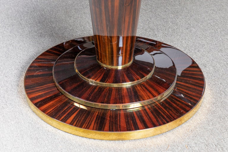 Round table top displays beauty of the high quality Macassar wood. It is supported by the slim leg that is attached to the round base. The top of the base has brass decorative elements wrapped around it.  Re-polished. Condition is
