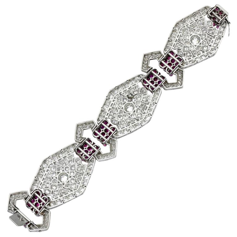 Of geometric design, this stunning Art Deco bracelet is composed of pierced hexagonal plaques spaced with buckle motifs, set with circular-cut rubies and single- and circular-cut diamonds, length approximately 175mm, French assay marks and maker's