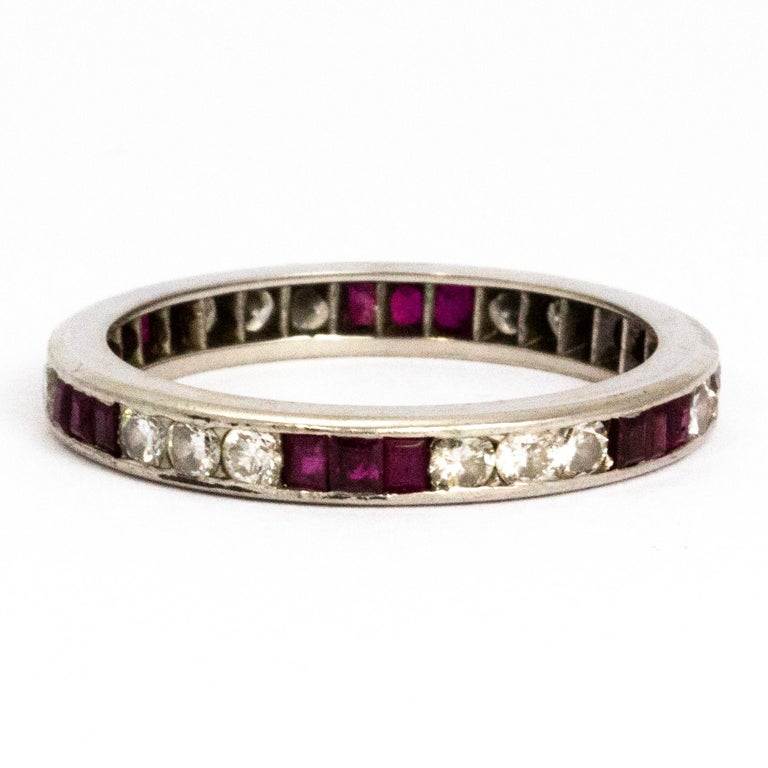 The gorgeous round cut diamonds measuring 5pts in this ring are perfectly complemented by the 10pt step cut rubies. The different colour and cut of stones make a really striking pattern on this full eternity band.   Ring Size: R 1/2 or 8 3/4