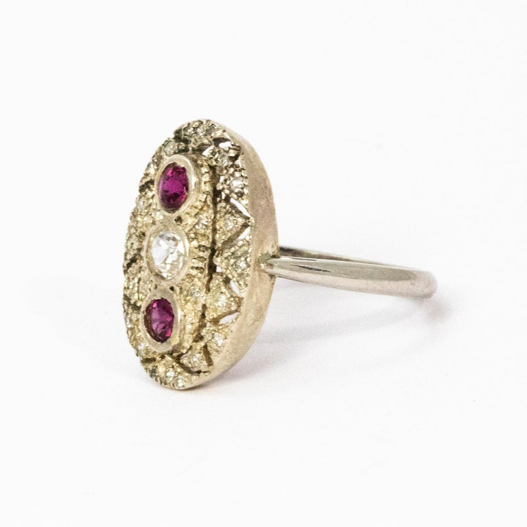 Stunning Art Deco period panel ring set with a central diamond and pink rubies above and below. This ring is is made up of open worked platinum.  Ring size: J or 4 3/4