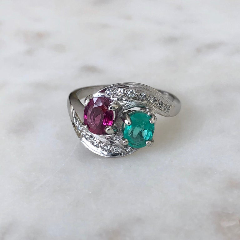 An Exclusive Antique Art Deco Toi et Moi Emerald Ruby Diamond Platinum Engagement Ring  Primary Stone: 100% Natural Ruby, Emerald and Diamond  Shape or Cut: Oval Cut Total Gemstone Weight: Approx. 1.73 Carat  Average Color Gemstone: Best Color