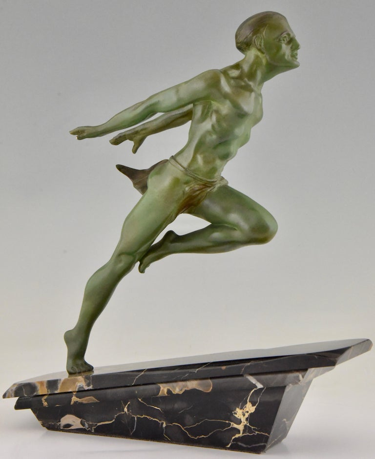 Art Deco running man statue by L Valderi French, circa 1930. Verdigris patina metal sculpture on sculpted portoro angled marble base. The movement of the man, reminiscent of the great male statue known by Jean de Roncourt. This one is signed L.