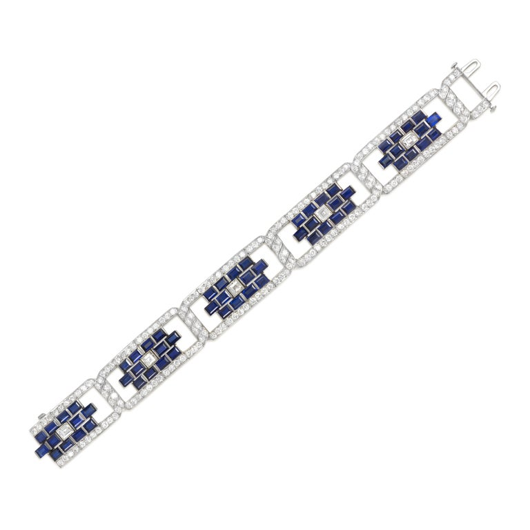 An Art Deco geometric emerald-cut diamond and sapphire plaque bracelet with twisted hinges and round-cut diamond frames, in platinum. Two different stamping hands #3174; 521 9.  Atw 8.15 ct. diamonds; atw 14.40 ct. sapphires.  Craftsmanship is