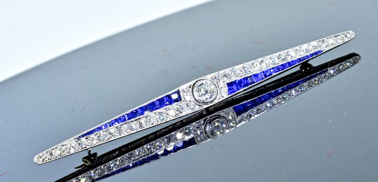 Art Deco platinum pin possessing 32 very fine calibre cut natural bright vivid blue sapphires weighing approximately .50 cts.  The white brilliant cut diamonds are all near colorless, G/H, and very very slightly included to very slightly included