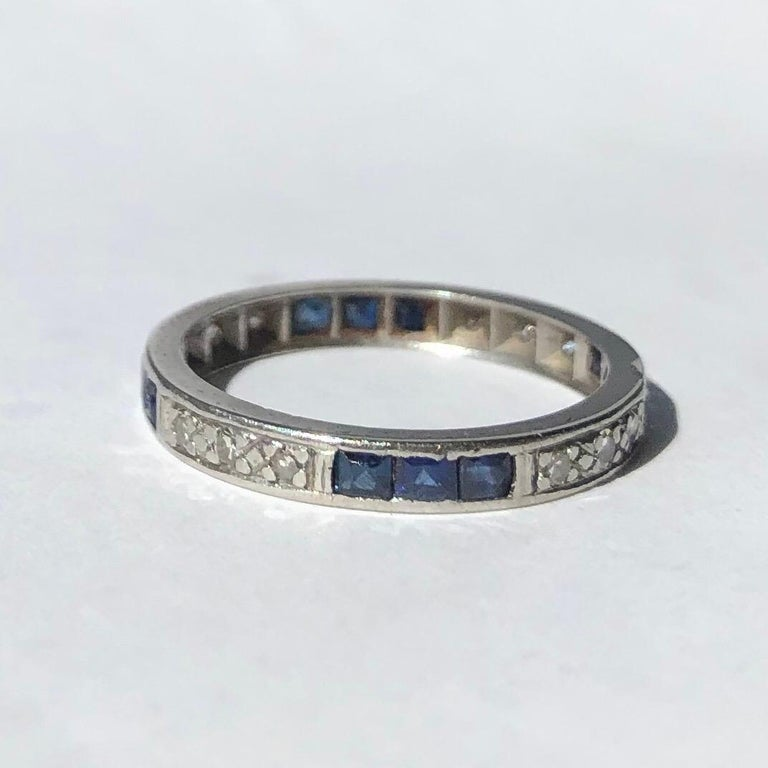 This eternity band holds sapphires and diamonds in clusters of three. The Sapphires measure 5pts each and the diamonds measure 2pts each. The stones are set within the platinum band.   Ring Size: M 1/2 or 6 1/2, Band Width: 2mm   Weight: 2.79g