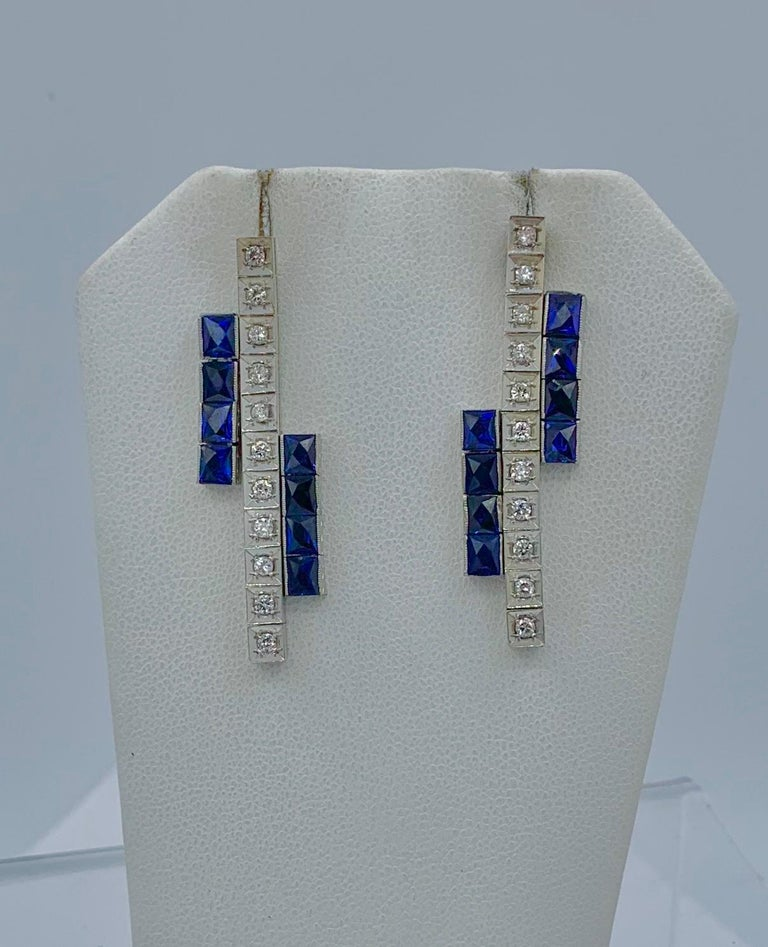 This is a stunning pair of Art Deco Sapphire and Diamond Dangle Drop Earrings in 14 Karat White Gold.  The fabulous earrings are articulated throughout so they dangle beautifully from the ear.  The earrings have 22 sparkling white diamonds set in