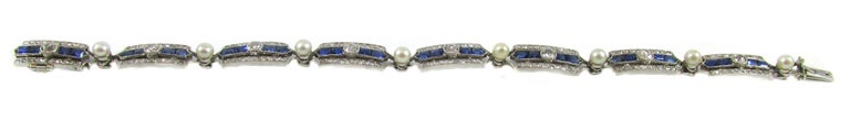 This amazingly hand-crafted French Art-Deco bracelet from ca. 1925 features 8 rectangular panels each set with 2 rectangular step-cut and 2 bullet-shape step cut royal blue sapphires. In the center of the sapphires, a bright white and sparkly Old