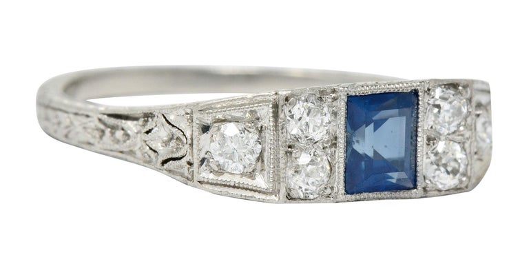 East/West style band ring centering a rectangular cut sapphire weighing approximately 0.50 carat; bright blue  Bezel set and flanked by old European cut diamonds weighing in total approximately 0.45 carat; G to I color with SI clarity  With a
