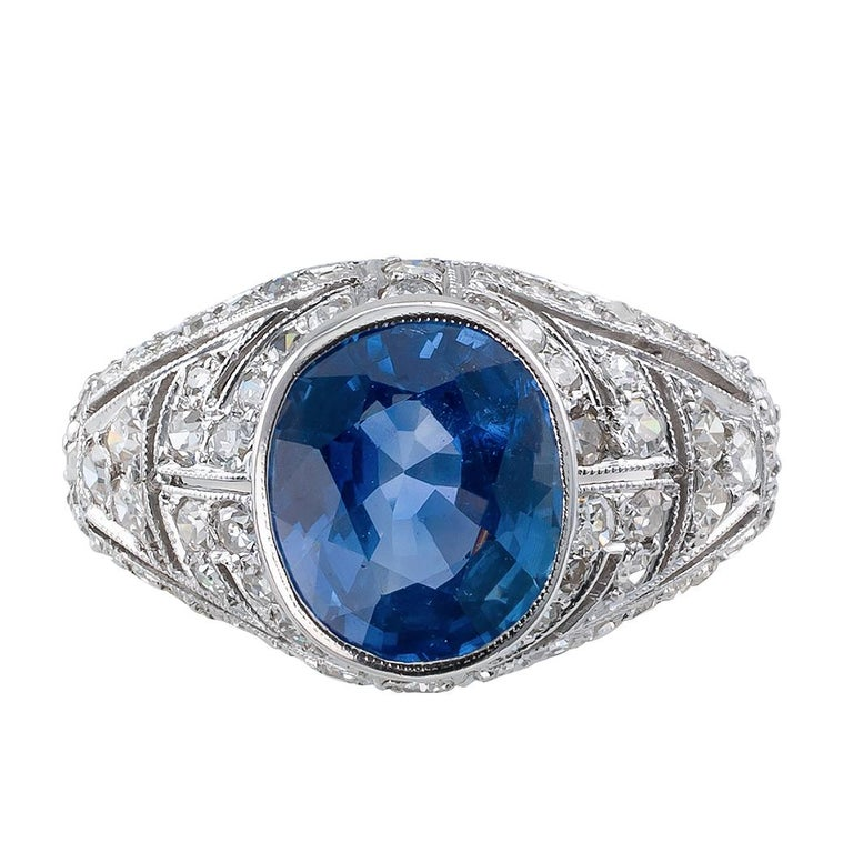 Art Deco sapphire and diamond platinum ring circa 1925. The design showcases a bezel-set, oval, blue sapphire weighing 2.47 carats, on a slightly domed platinum mounting decorated by open work, geometric motifs and milgrain, entirely frosted with