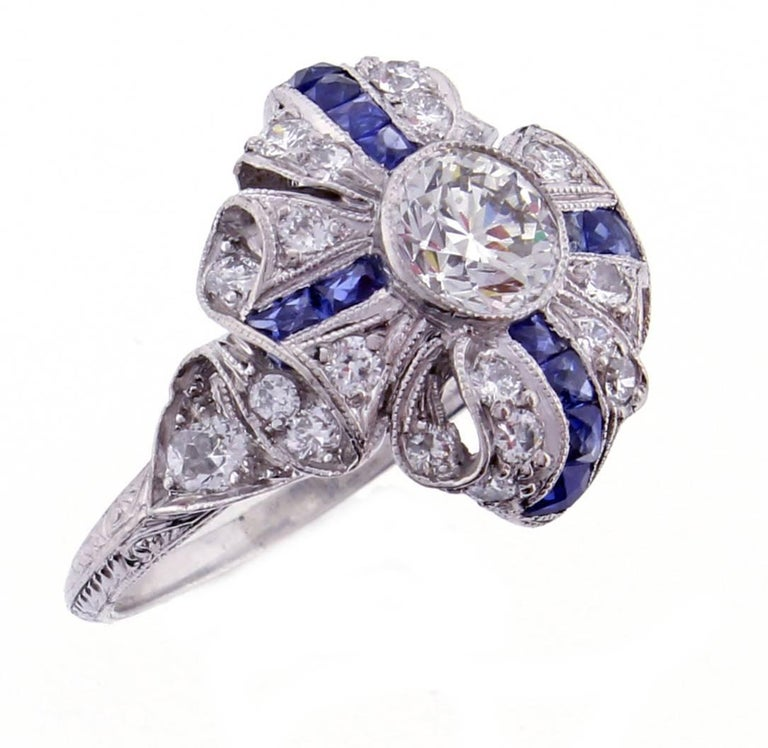 An exceptional example of Art Deco style and craftsmanship. The platinum ring is designed as a ribbon folding in upon itself. The center old European cut diamond weighs approximately .75 carat, H color and VS1 clarity. Accented by 12 french cut