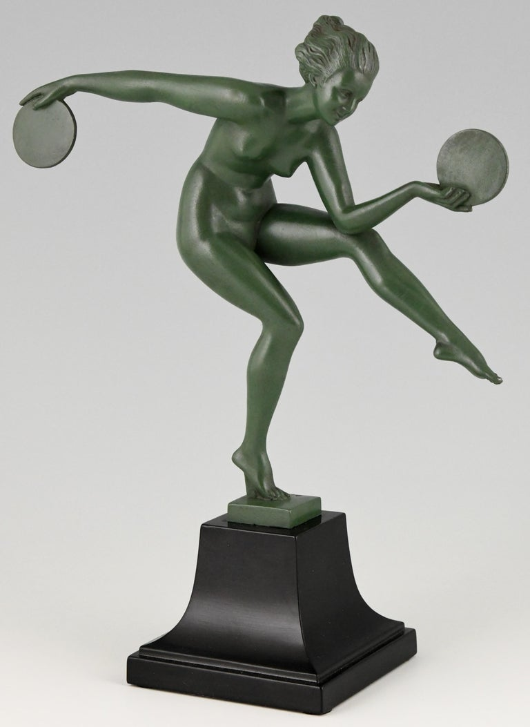 Elegant Art Deco sculpture of nude disc dancer by Derenne. Pseudonym used by Marcel Bouraine for his art metal sculptures cast by the Max Le Verrier foundry. This sculpture is in Art metal with a green patina and stands on a black metal base,