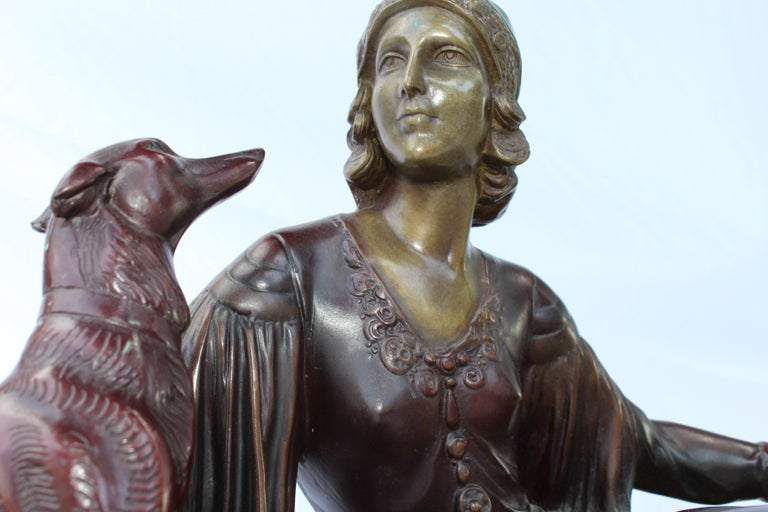 A hi-quality Heavy bronze figurine of elegant lady sitting with her dog. Her title is (Desdemona) cast from the original by the Artist Mennivale from the 1920s. Multi patinas and mounted on a marble and onyx base. Medium size bronze and heavy. Looks