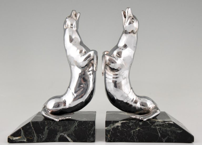Nice pair of Art Deco seal bookends signed by the French artist Louis Albert Carvin, polished white metal on a green marble base, France, 1930. 