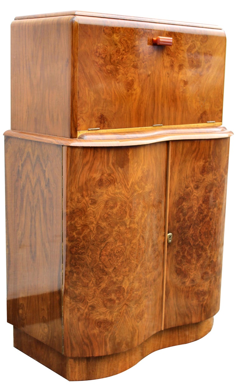Beautiful 1930s Art Deco walnut serpentine shaped cocktail cabinet in gorgeous figured veneers, every Deco interior should have one of these! Features a drop down top which reveals an all mirrored interior which acts as storage for glasses. Still