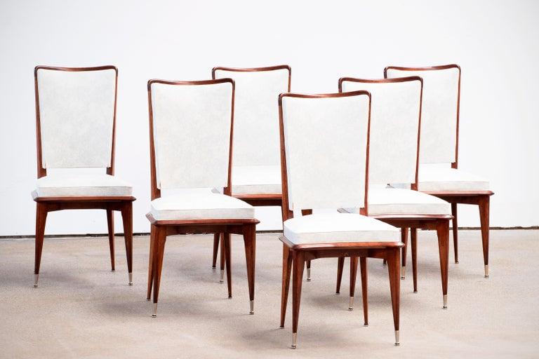 Set of six upholstered high back chairs covered in white vynil, exhibiting traditional French design elements in a deep oak finish. Restored and polished.