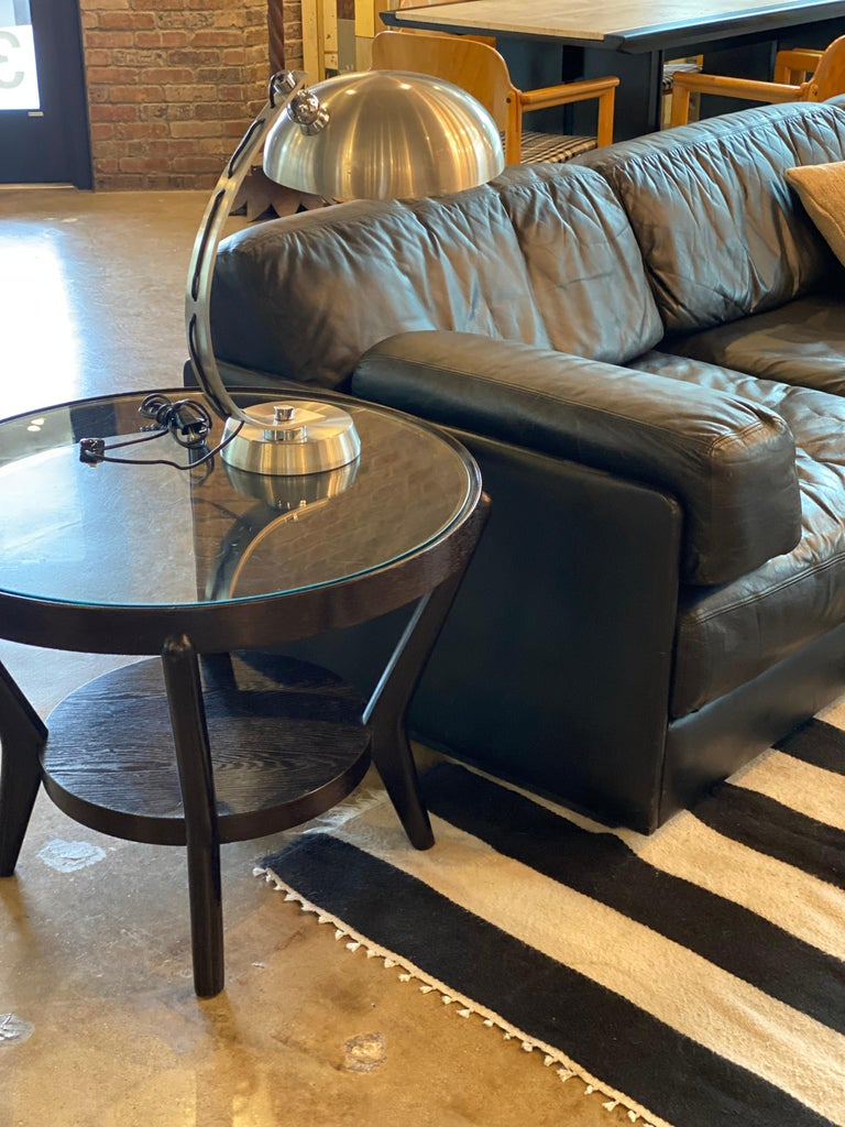 Art Deco round side table with wood frame (dark brown to ebony), lower wood shelf and round glass top. Two available, sold separately, Europe, 1930s-1940s.