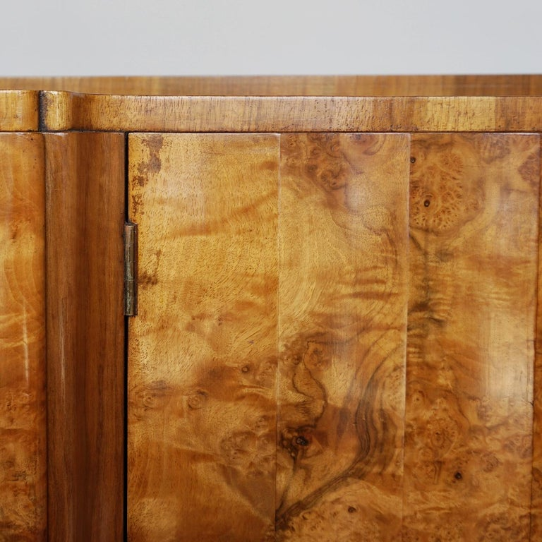 An Art Deco sideboard by Harry & Lou Epstein. Central drawer and bottle storage compartments fronted by fluted burr walnut doors, flanked by two burr walnut fronted shelf compartments. Burr walnut veneered to top, with figured walnut to sides and