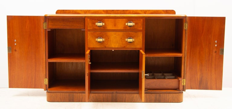 Art Deco sideboard credenza in a beautiful bird's-eye maple and walnut. Irish Art Deco sideboard with Waterfall Edges & Bakelite handles. Two large cupboard doors to flanks Two central drawers above small central cupboard section Internal