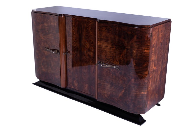 Art Deco sideboard / credenza featuring a solid mahogany frame veneered in luxurious rosewood and finished in a high gloss lacquer. The piece has two single side doors with original brass hardware. Plenty of storage. French foot stained in a darker