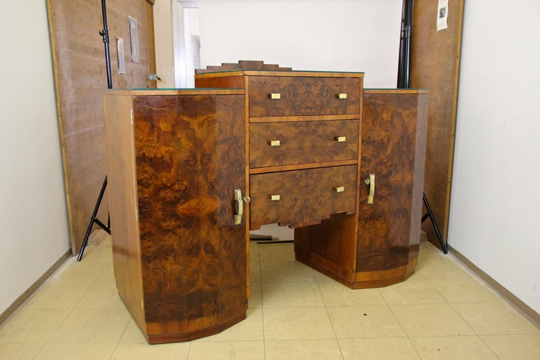Unique designed Art Deco sideboard or buffet out of Austria from the period circa 1925. This unusual shaped side board impresses with an absolute great book matched burr walnut veneer, giving it a real mesmerizing grain. The exceptional design with