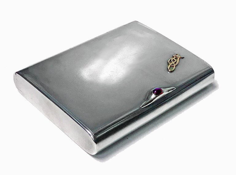 Art Deco silver cigarette case box, Estonia, circa 1925. Plain, flush hinge, cabochon red garnet thumb piece, gilded interior. No monograms, gold (tested) intertwined nouveau celtic insignia applied at one cornice, original patina, extremely light