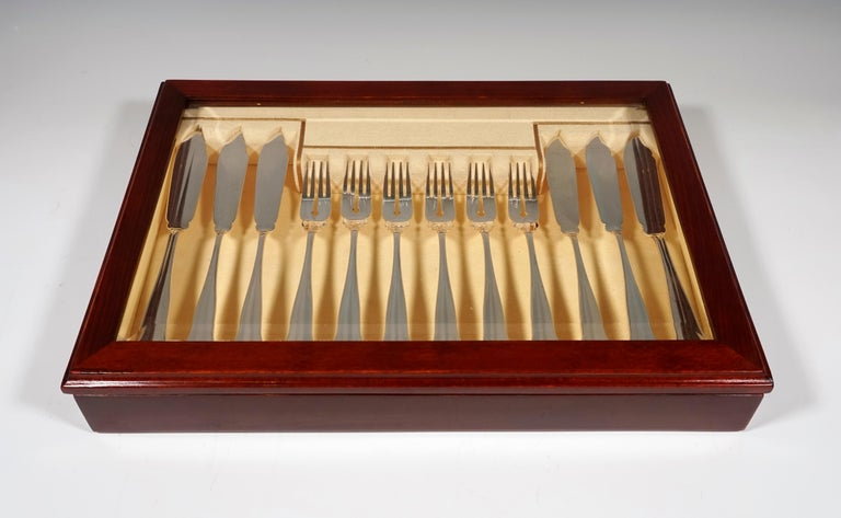 Elegant fish cutlery set made of solid silver for six people, consisting of 12 parts, in a showcase. Date of manufactory: circa 1925 Material: Massive sterling silver '800' Style: Discreet thread decoration around a slightly curved bridge with a