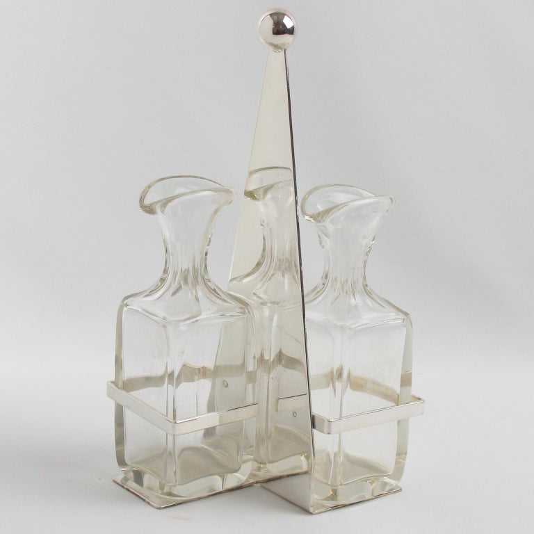 Lovely 1930s Art Deco modernist tableware serving set designed by Quist, Germany. Geometric base build in silver plate with tall handle finished by a metal ball finial. Two cut crystal bottles or containers for oil and vinegar with a geometric shape