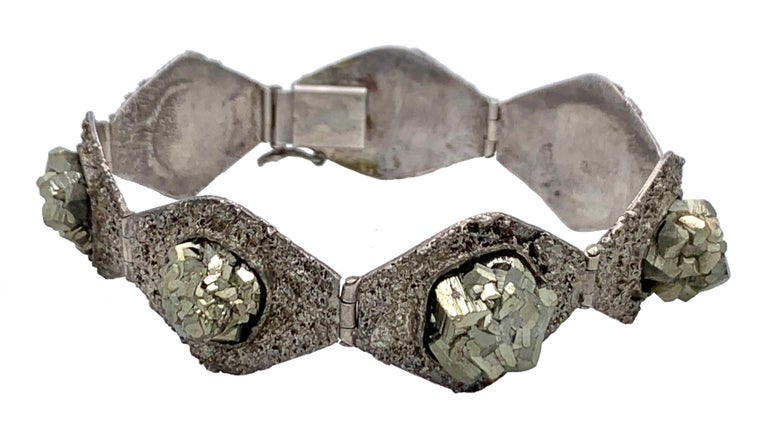 This very unusual and elegant  bracelet is made out of seven lozenge shaped textured links. Each link is set with a large pyrite cubic crystal. The bracelet is marked in the tongue of the clasp with the german 800 silver mark. There  is a makers