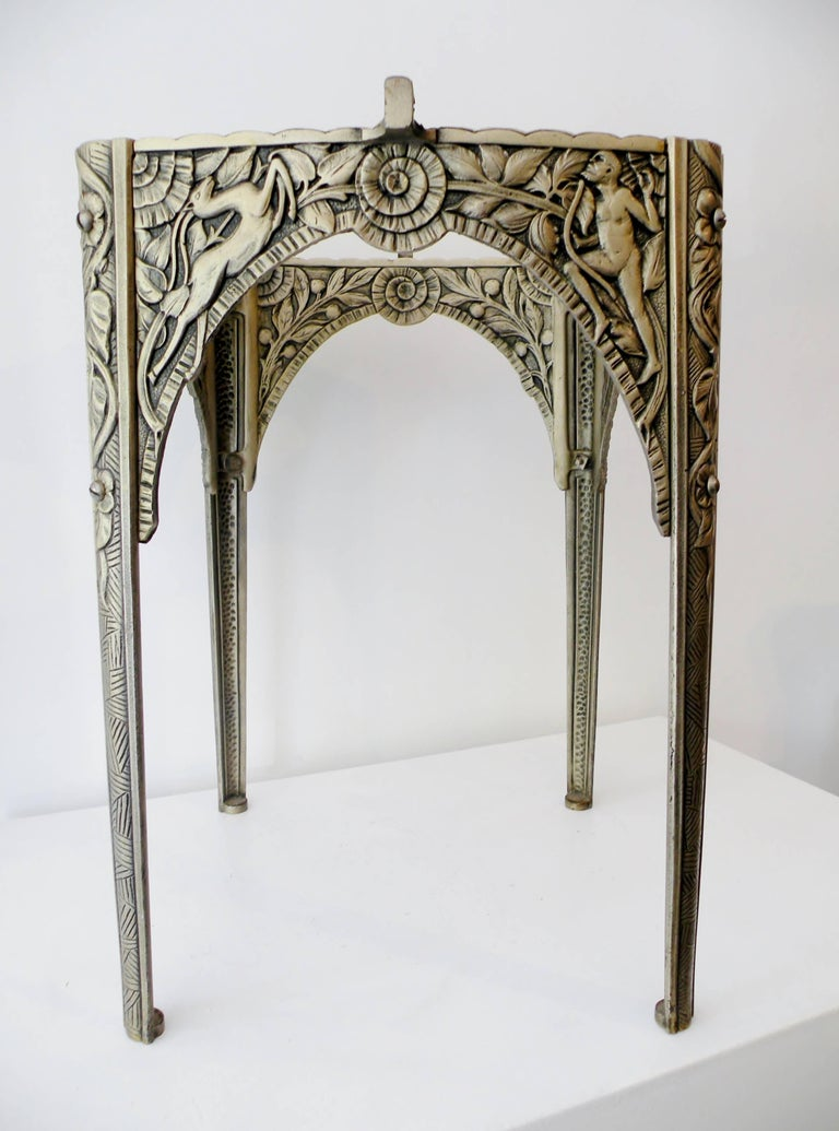 Finely detailed Art Deco cast iron cocktail accent table depicting scenes of Satyre and gazelle with folliage. Decoration extends to the interior as well. Silver and old clear lacquer surface finish. Unmarked and similar in design and manufacture to