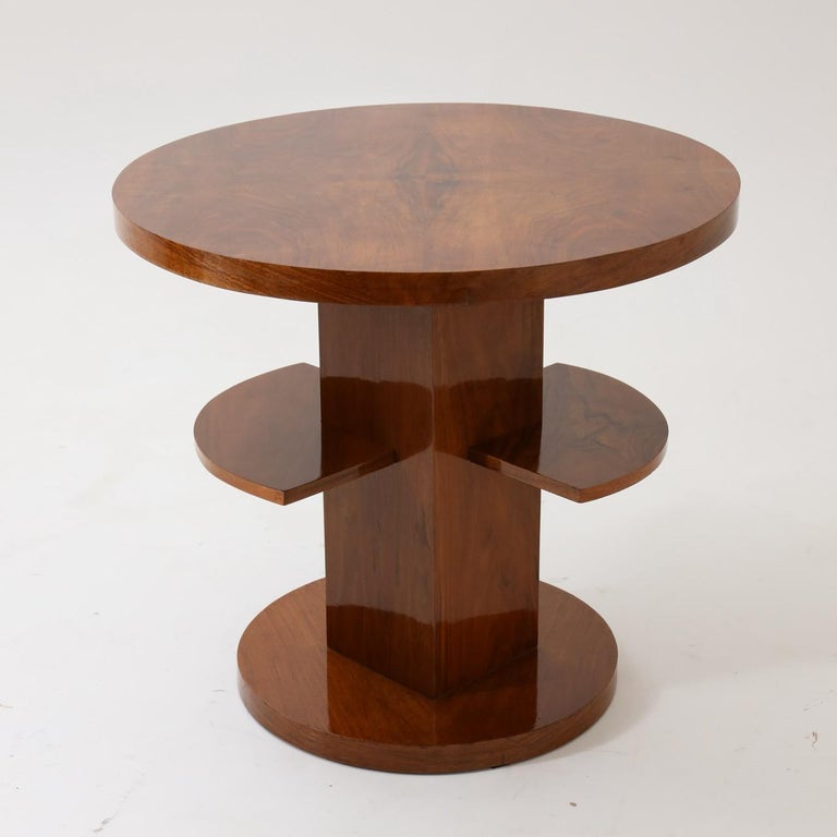 An Art Deco round side table.  Walnut with central support featuring two smaller shelves resting on a round base.
