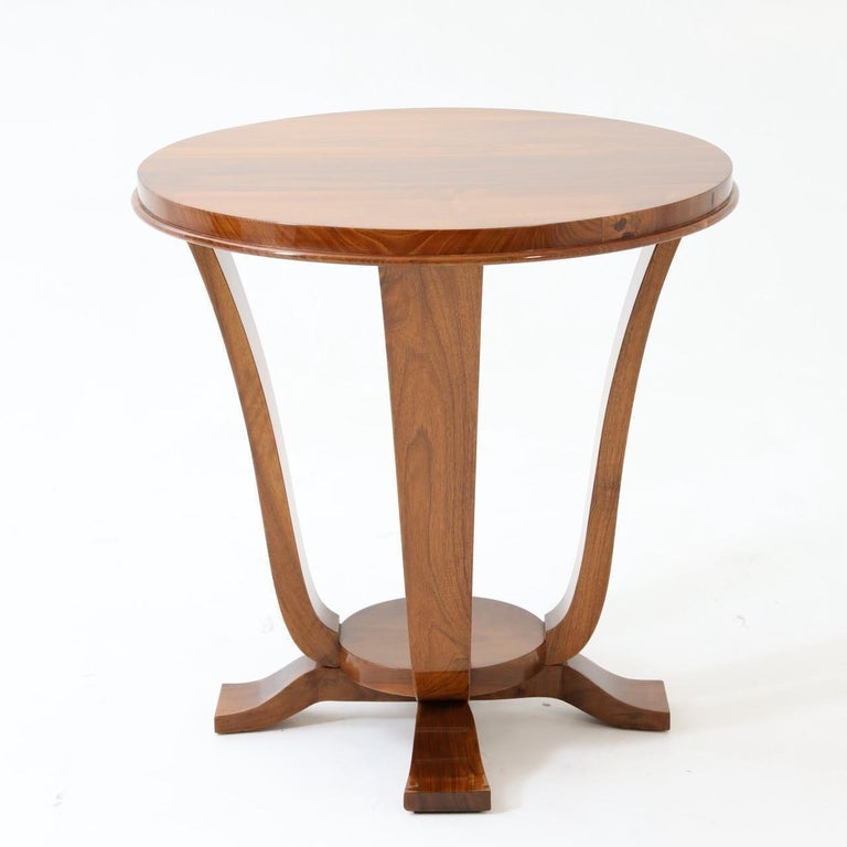An Art Deco round side table.  Walnut with four curved legs resting on a footed base.