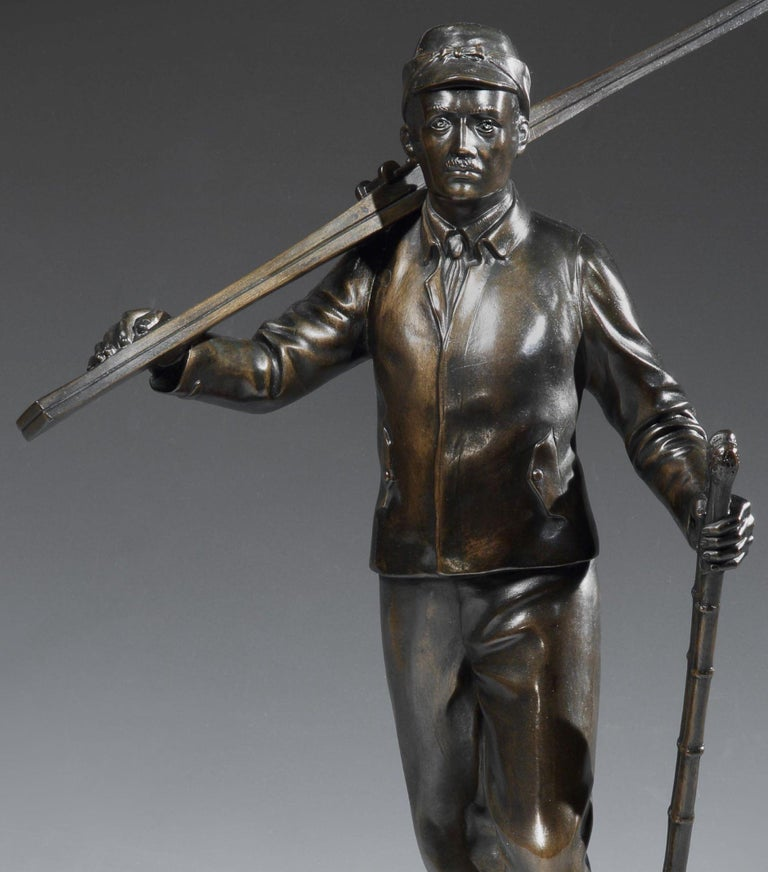 A strong figurative ski bronze in the German School style, of a male skier walking through the snow with his skis over his shoulder and sticks in his hand. The warmly patinated figure stands on a deep, tapering bronze sôcle signed H.S. MÜNCHEN and