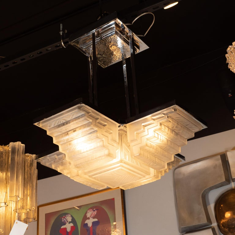 This stunning and dramatic Art Deco chandelier was realized by the storied atelier, Sabino, in France circa 1935. It features four frosted glass rectangular skyscraper style