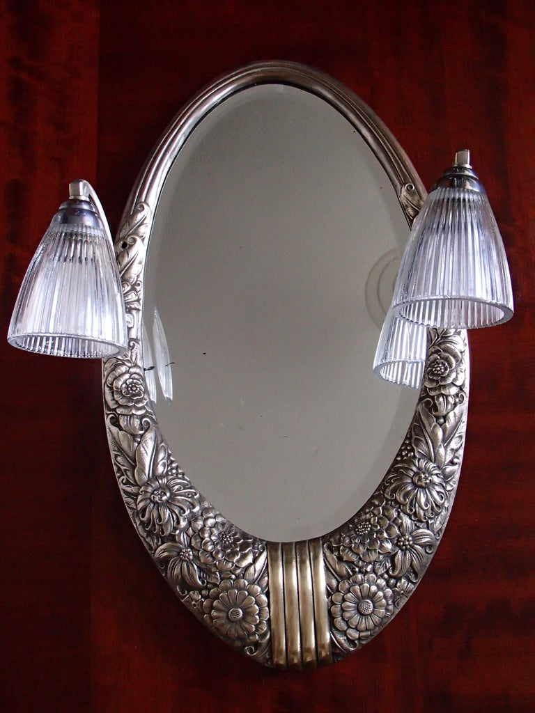 Art Deco small floral brass wall mirror with pair of lights.