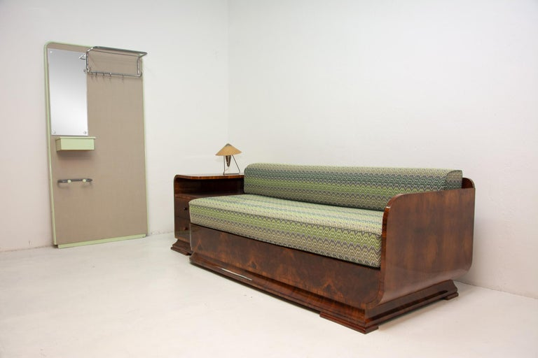 This Art Deco sofa was made in the 1930s in the former Czechoslovakia. The piece is an example of the Czechoslovak Pre-war Art Deco style and it features a wooden structure that is veneered in the walnut and a storage space. Sofa is in excellent
