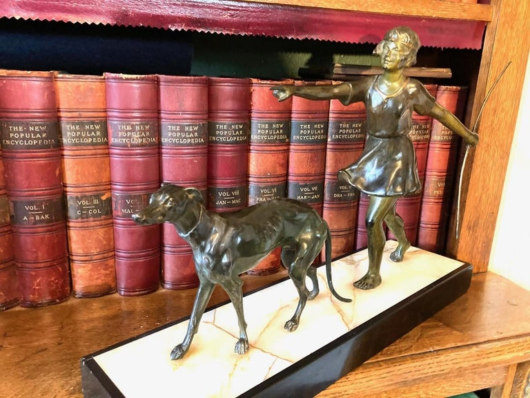 Attractive and charming Art Deco figure of a young girl walking her dog. This delightful figure is in excellent condition and retains a mellow antique patination. It has taken pride of place in my study for 20 years or more and downsizing means she