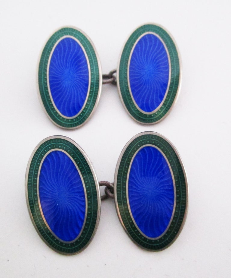 These remarkable Deco cufflinks are in sterling silver and enamel, featuring a rich royal blue and bright green guilloche enamel fields. The links are characterized by their brilliant, saturated colors and sleek oval shape. The striking color scheme