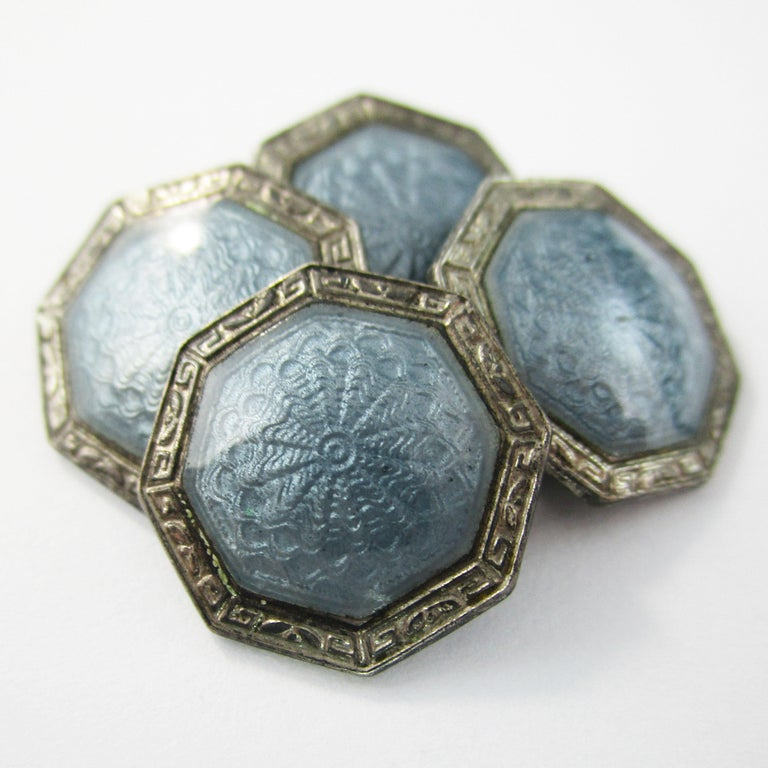 This is an excellent pair of Art Deco cufflinks in sterling silver with gorgeous gray guilloche enamel panels. The enamel is in incredible condition and has a subtlety of detail that creates a reflective, dimensional appearance. The enamel has a
