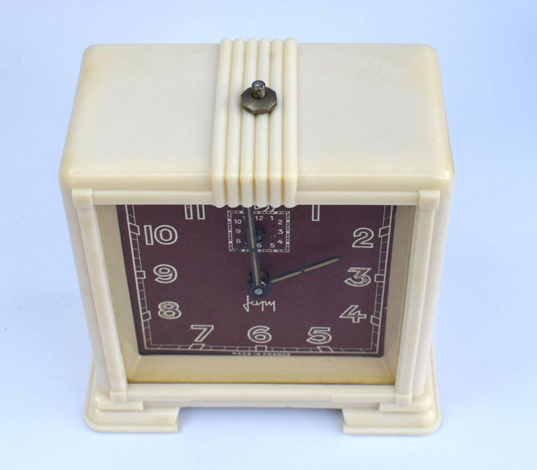 Lovely Art Deco French clock by the French clock makers Japy. Streamline bakelite casing with maroon colored dial. Fully serviced and keeping good time.