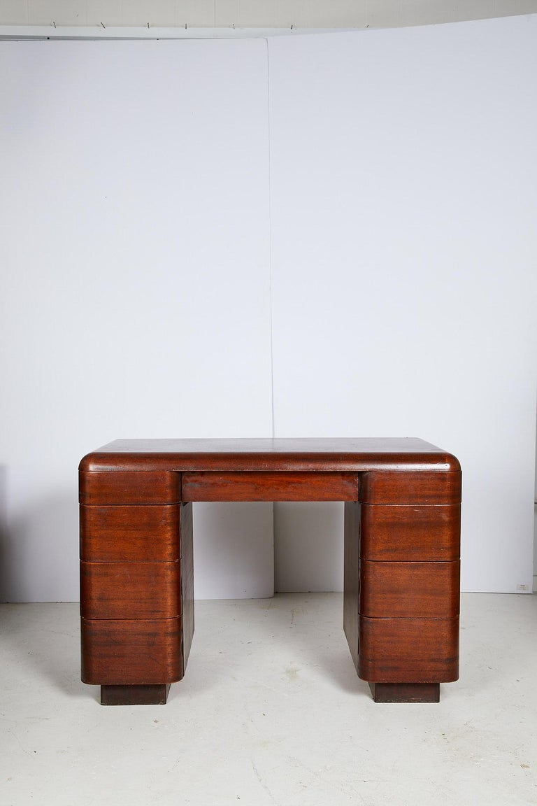 The 20th century streamlined writing desk was designed by Paul Goldman in 1946 for Plymold Co. in the Art Deco style. The bentwood desk holds a shallow center drawer flanked by pedestals with eight graduated drawers that are flushed into the case