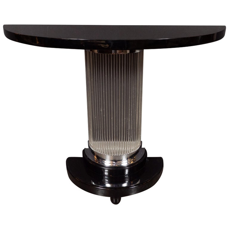 This stunning Art Deco Machine Age console table was realized in the United States, circa 1935. It features a streamlined demilune form black lacquer top with a stepped skyscraper style base of the same shape with chrome detailing and rounded