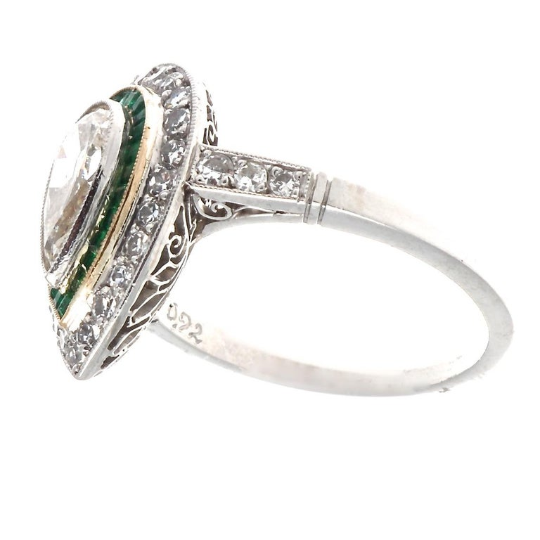 The prettiest vintage pear shaped diamond is the star of this ring show. This Art Deco inspired design features a gorgeous pear shaped diamond just under 1 carat. Adorned by 31 glittering single cut diamonds and 26 calibré emerald cut emeralds, this